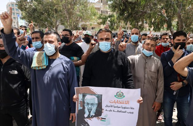 Supporters of the Hamas movement take part in a rally against the decision of the Palestinian authorities...
