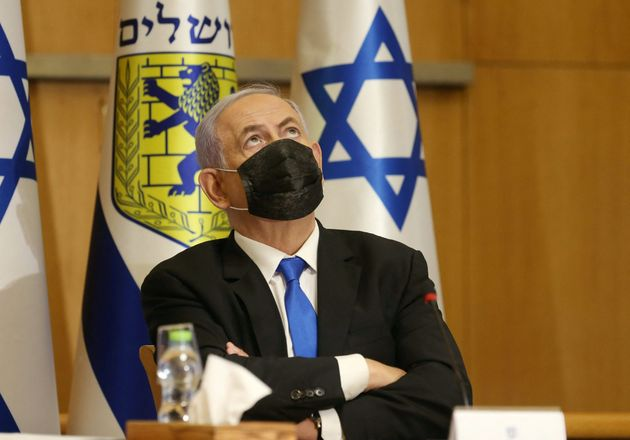 Israeli Prime Minister Benjamin Netanyahu, wearing a mask for protection against the COVID-19 pandemic,...