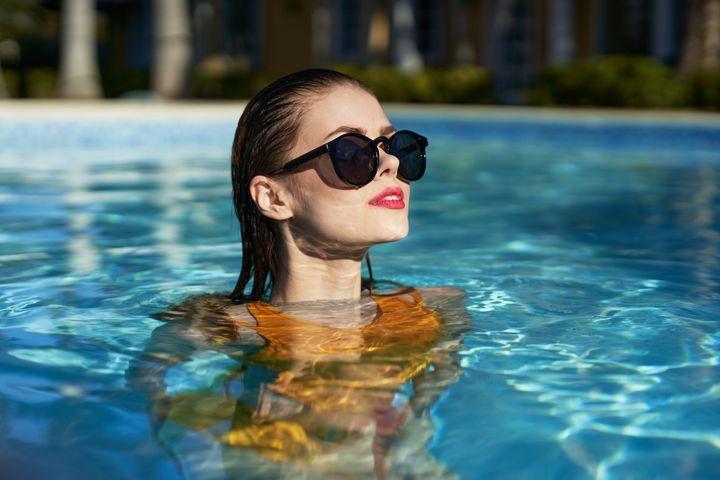 Chica en la piscina con gafas de sol