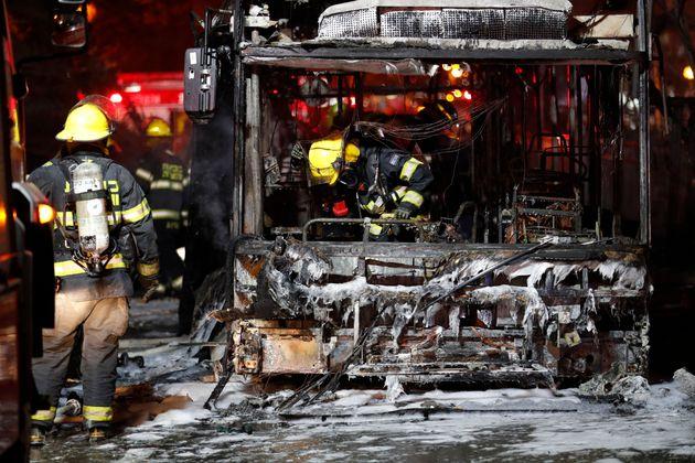 Bomberos israelíes revisan un autobús quemado en la ciudad israelí de Holon cerca de Tel Aviv, el 11...