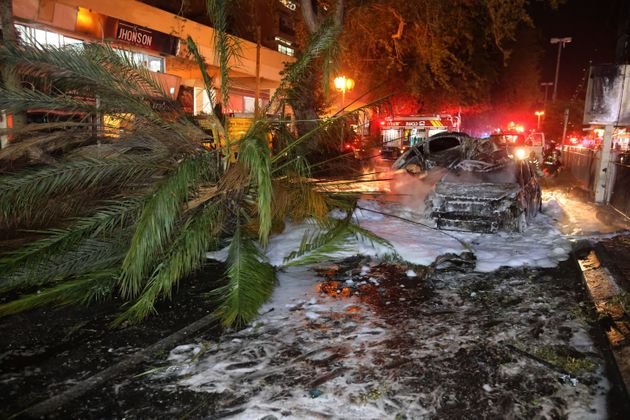 Israeli firefighters extinguish burning cars in the town of Holon near Tel Aviv, on May 11, 2021, after...