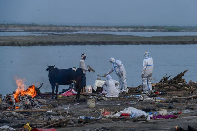 TOPSHOT - Relatives in personal protective equipment (PPE) suits perform the last rites before the cremation...