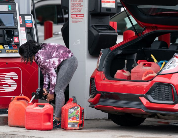 A woman fills up several gasoline cans Wednesday at a Speedway gas station in Benson, North Carolina. Most stations in the ar