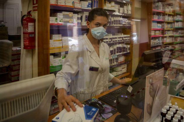 Una farmacéutica atiende a un cliente en