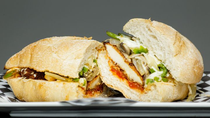 Chicken parm sandwich on a plate against a gray background. Some of the ingredients include chicken, onions, green peppers, mozzarella