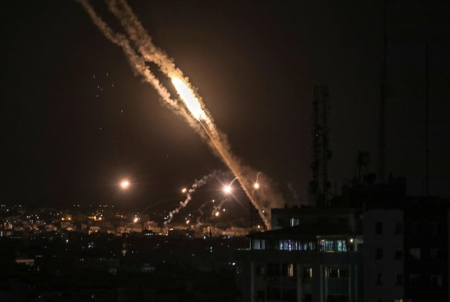 epa09198335 Rockets fired from Gaza fly towards Israel, as seen from Gaza City, late 13 May 2021. In...