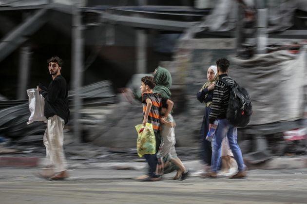 epa09198376 A Palestinian family flee from their house in Al Shejaeiya neighborhood during Israeli air...