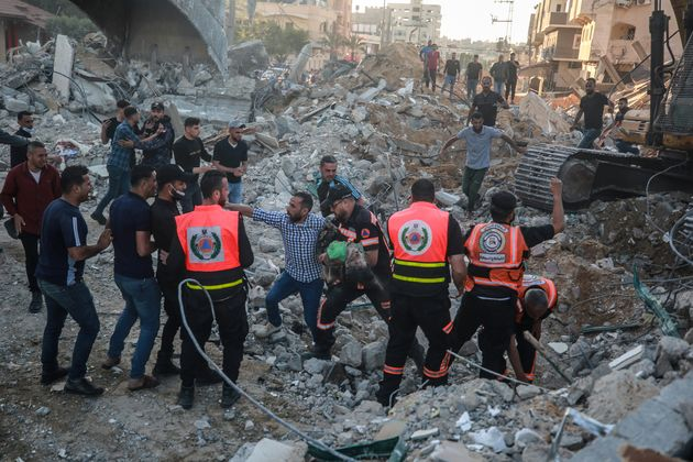BEIT LAHIA, GAZA - MAY 13: Palestinian civil defense teams take part in rescue works to pull out a body...