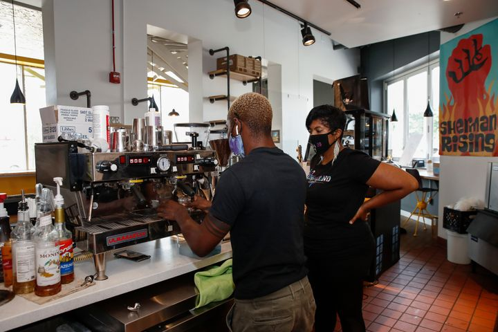Baboonie Tatum, owner of the Rise & Grind Cafe, checks on an employee inside her coffee shop in Milwaukee on Aug. 15, 202