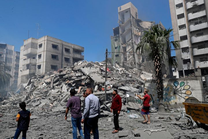 People insect the the rubble of the Yazegi residential building that was destroyed by an Israeli airstrike, in Gaza City, Sun