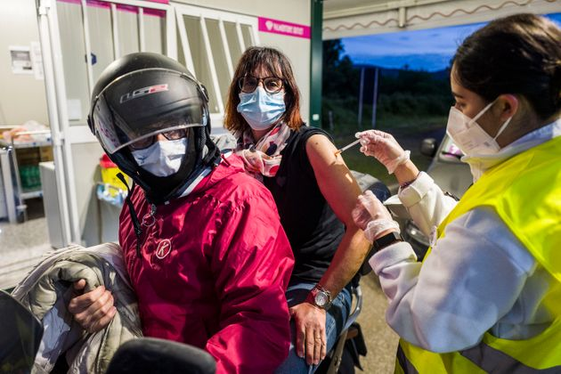 ROME, ITALY - MAY 15: A nurse inoculating a woman on a motorbike with the Astrazeneca vaccine at the...