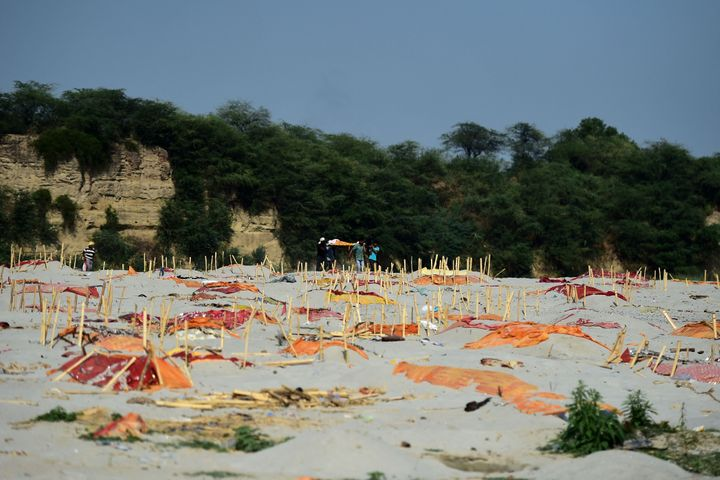 Relatives carry a dead body past shallow graves covered with saffron clothon the banks of the Ganges River in Shringver