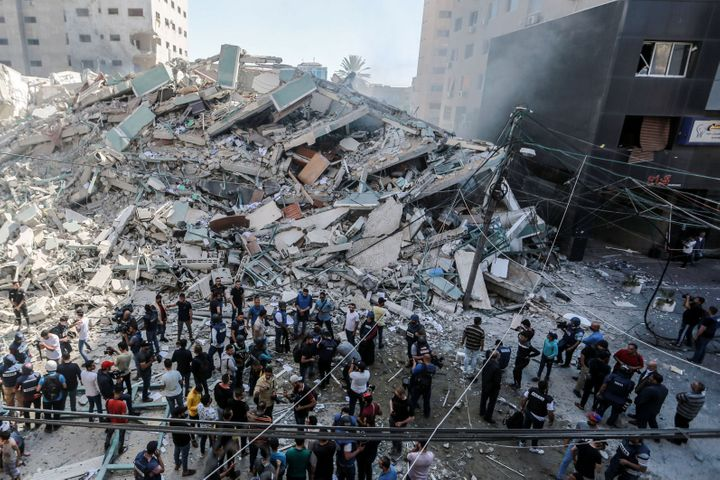 Palestinians inspect the remains of Al-Jalaa tower, which housed several media outlets including The Associated Press and Al