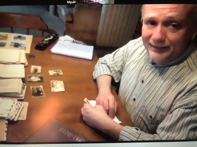 オンラインでの取材に答えるデビッド・ワッセルさん=2021年5月9日。手前にある5枚の写真はハリーさんが戦地で拾ったもの。デビッドさんは「日本の家族のもとに返したい」という