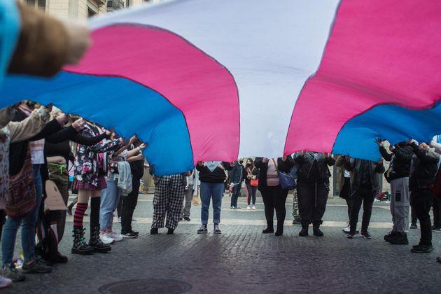 Varias personas con una bandera trans en una protesta a favor de la