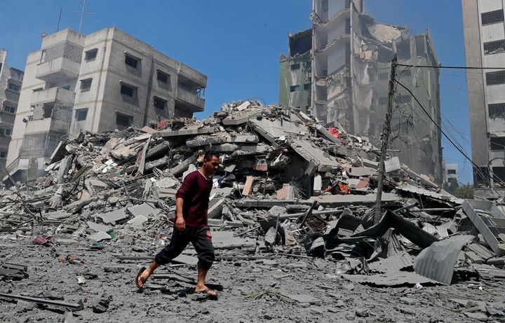 A man walks past the the rubble of the Yazegi residential building that was destroyed by an Israeli airstrike, in Gaza City,