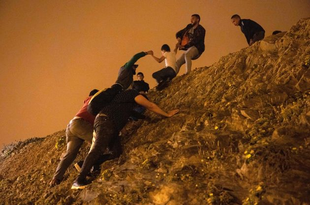 Moroccan migrants climb a rocky cliffside as a policeman watches in the northern town of Fnideq as they...