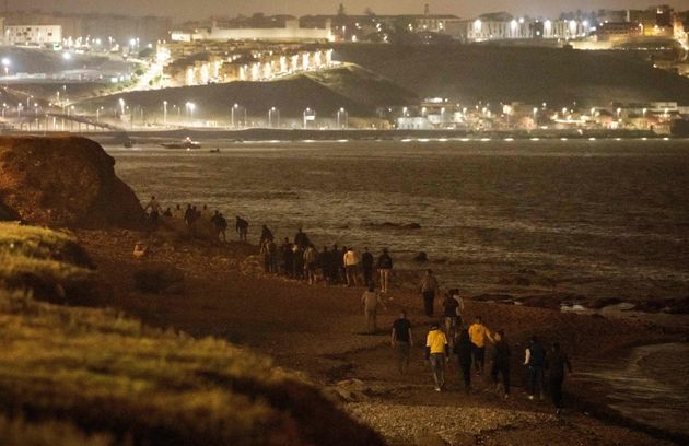 Moroccan migrants walk on the sea shore towards a rocky cliffside in the northern town of Fnideq as they...