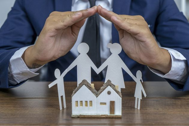 Insurer protecting a family with his hands; multiple