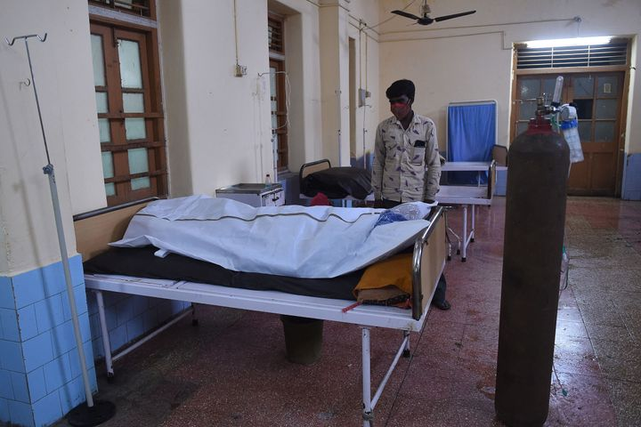 A family member mourns next to the body of a COVID-19 victim in a hospital in Mahua on May 18, 2021.