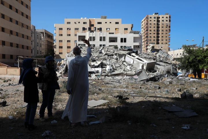 A Palestinian man stands near the remains of a building after it was destroyed in Israeli air strikes in Gaza City on May 18,