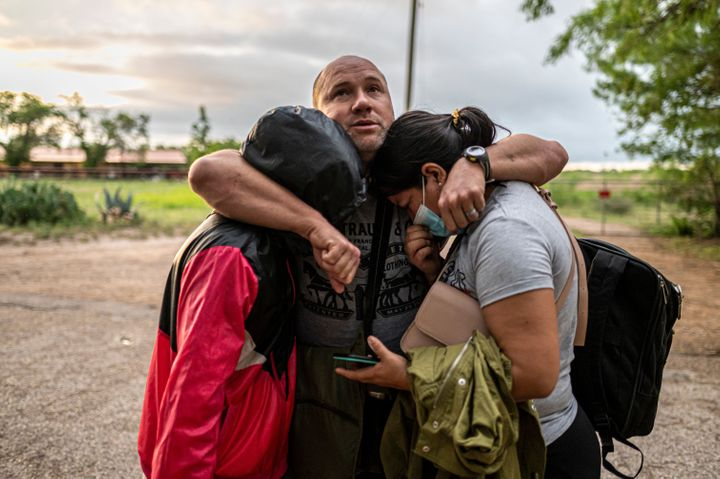 A migrant man embraces his wife and daughter after crossing the Rio Grande near the border between Mexico and the United Stat