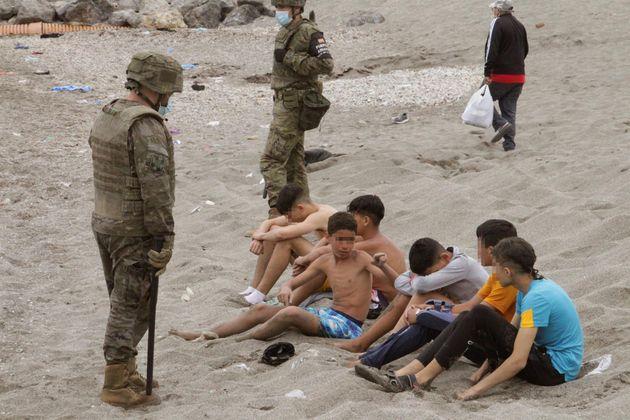 Miembros del Ejército de Tierra vigilan a un grupo de inmigrantes menores que han logrado cruzar uno...