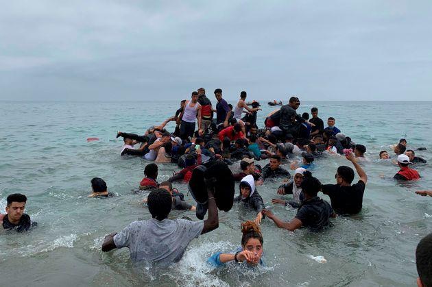 Un grupo de personas se hacen con una embarcación de las autoridades marroquíes en la playa de la localidad...