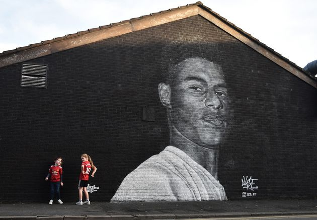 Two young girls pose for a photograph at a mural of Manchester United footballer and child poverty campaigner...