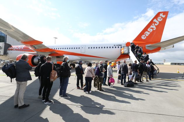 Passengers prepare to board an easyJet flight to Faro, Portugal, at Gatwick Airport on