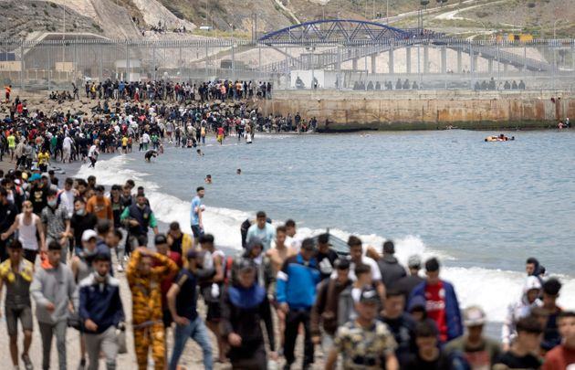 Migrants are pictured between Morocco and the Spanish enclave of Ceuta on May 18, 2021 in Fnideq. - At...