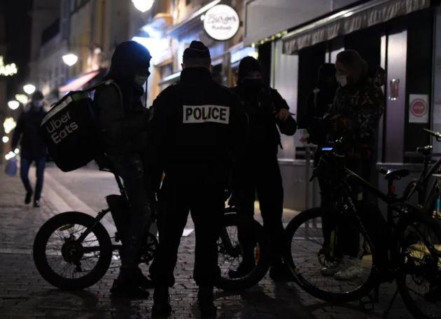Un policier vérifiant l'attestation d'un coursier pendant le couvre-feu. Image
