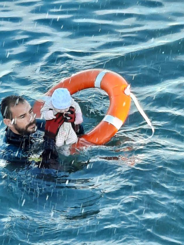 Un neonato viene soccorso a Ceuta, in una foto twittata dalla Guardia