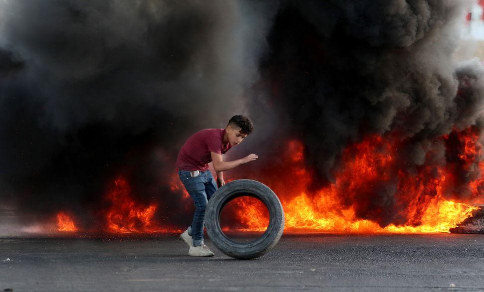 Nablus, Cisgiordania. Un giovane palestinese dà fuoco alle gomme in risposta all'intervento delle forze...