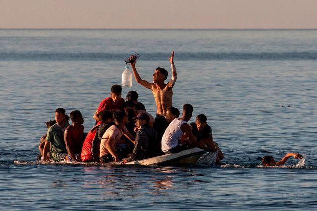 Un grupo de inmigrantes intenta cruzar a España a bordo de una barca cerca de la playa ceutí de El Tarajal,...