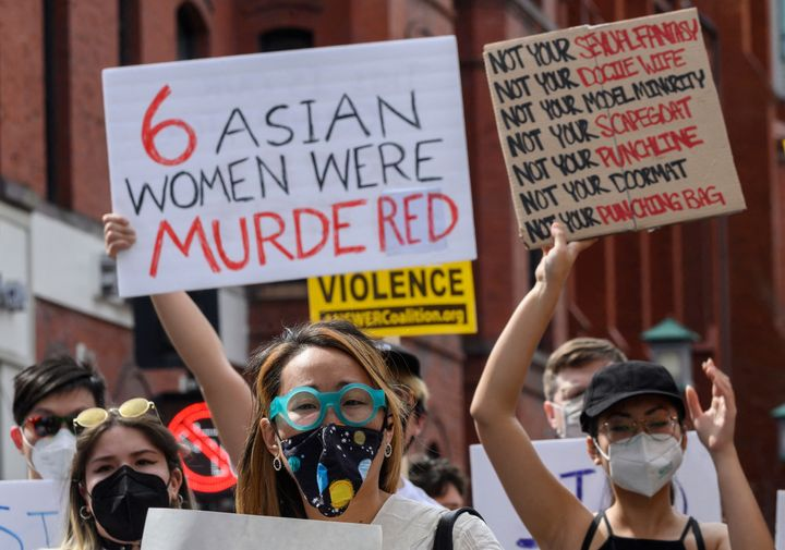 """Asian women at a protest in Washington's Chinatown on March 27, 2021. One woman holds a sign that reads """"6 Asian women were m"""