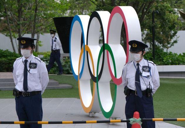 Dos vigilantes protegen una escultura de los aros olímpicos por una protesta ciudadana en