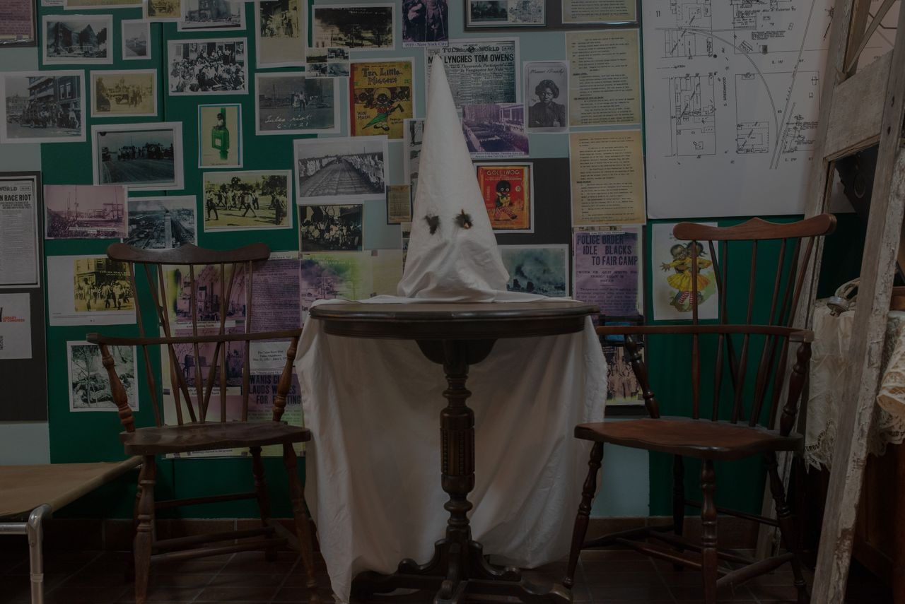 A historical collection on Oklahoma from before the end of slavery to the present sits behind the shops of the historic Greenwood district. A KKK hood rests on a table in front of an exhibit on the 1919-1921 period.