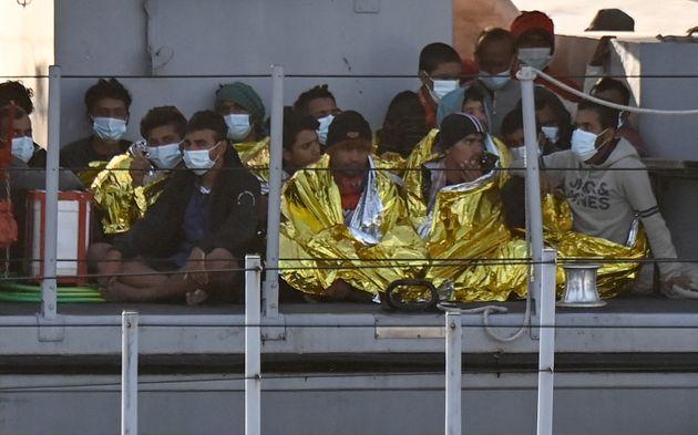 Migrants warmed by emergency blankets arrive on a boat of the Italian Guardia Di Finanza law enforcement...