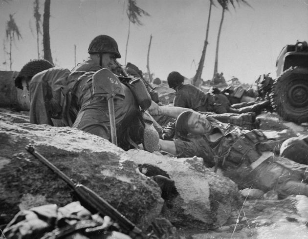 American marine dragging a dead comrade out of the surf as others duck machine gun fire from Japanese...