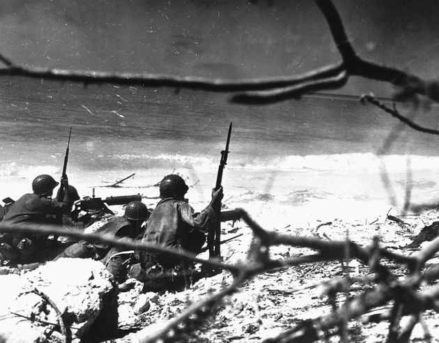Marines of the 22nd Regiment aim machine gun fire at a Japanese target 400 yards up the beach at Eniwetok...