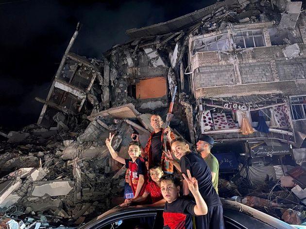 Un grupo de palestinos hacen gestos de victoria ante un edificio destrozado por las balas, anoche, en...
