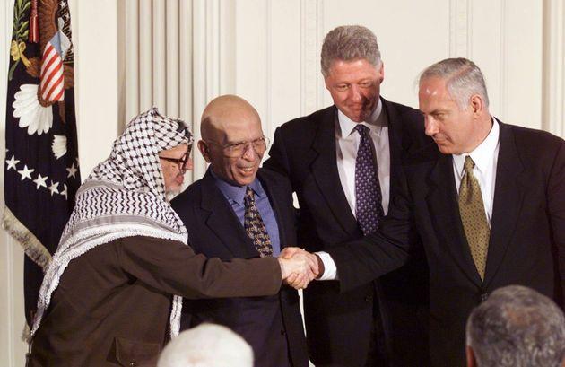 Yasser Arafat y Benjamin Netanyahu se dan la mano, en presencia de Hussein de Jordania y Bill Clinton,...