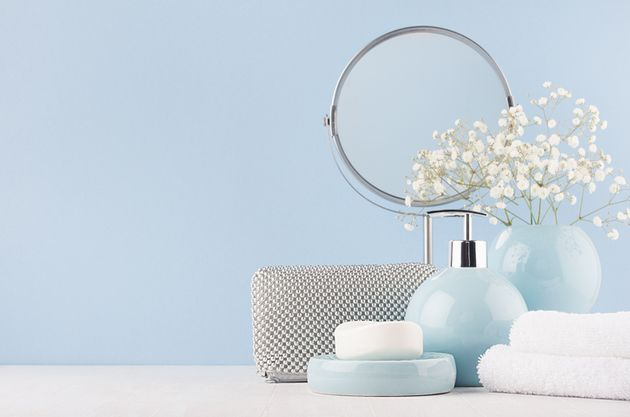 Bathroom decor for female in light soft blue color - circle mirror, silver cosmrtic bag, white flowers,...