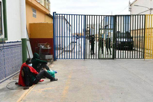 Dos hombres esperan a que les atiendan a las puertas de un centro en El