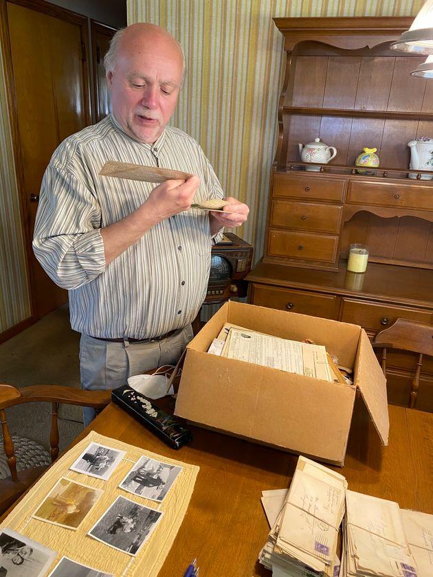 遺された手紙や写真を保存ボックスから取り出して見入るデビッドさん=2021年5月、Davidさんの自宅。福山万里子さん撮影