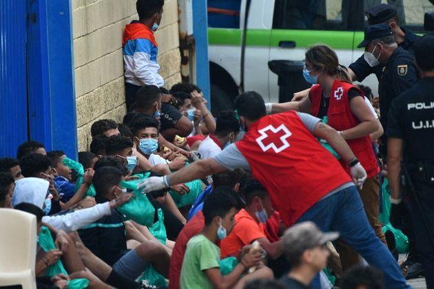 Des membres de la Croix-Rouge portent secours à des migrants à Ceuta, le 19 mai 2021 (photo