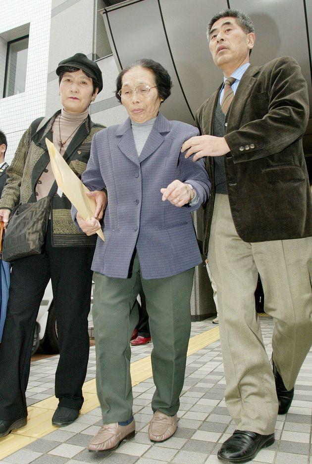 福岡高裁宮崎支部で再審開始が取り消され、支援者に支えられて記者会見場を後にする服役した原口アヤ子さん(中央)=2004年12月09日、宮崎市の宮崎県弁護士会館