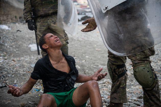Un migrante reacciona mientras habla con soldados españoles en la playa de Tarajal después...