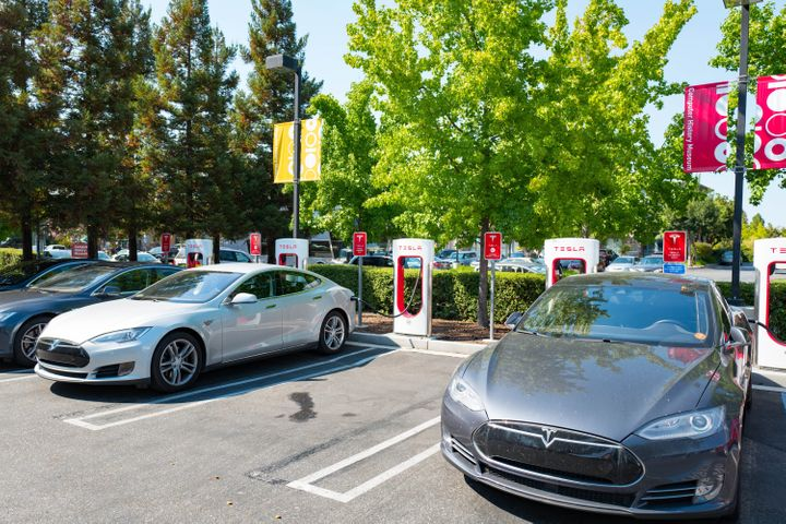 Several Tesla automobiles plugged in and charging at a Supercharger rapid battery charging station for the electric vehicle c